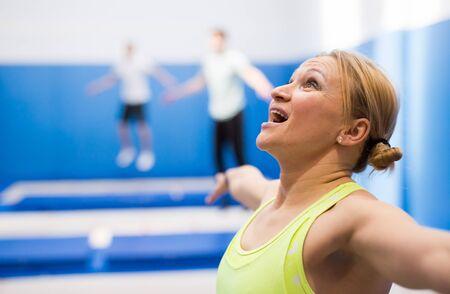 Photo pour Close up portrait of athletic woman training in indoor trampolines center - image libre de droit