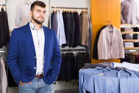 Photo for Brunette male customer choosing jacket in men clothes shop - Royalty Free Image