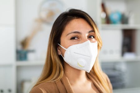 Photo pour Portrait of young mexican woman in mask in the modern office - image libre de droit