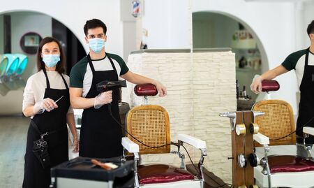 Portrait of male and female skilled hairstylist wearing protective face masks and gloves standing in modern hair studio, ready to work after coronavirus outbreak