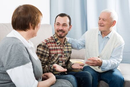 Photo for Elderly grandparents friendly conversation with grandson sitting on sofa - Royalty Free Image