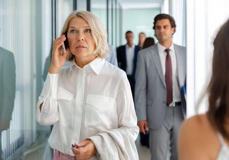 Photo pour Portrait of adult business woman talking on mobile phone in office - image libre de droit