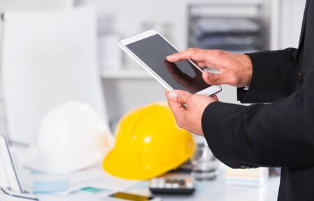 Photo pour Businessman holding and using smartphone at workplace in office - image libre de droit