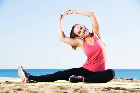 Photo pour Young positive girl doing yoga at beach on a sunny day - image libre de droit