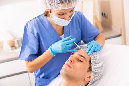 Photo for Young man patient of beautician receiving rejuvenating facial injections, concept of male aesthetic skin care - Royalty Free Image
