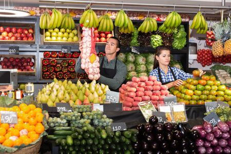 Foto für Male and female shop assistants laying out fruits and vegetables behind the counter on market - Lizenzfreies Bild