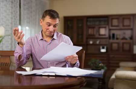 Photo pour Emotional man calculating domestic budget and checking accountancy at home table - image libre de droit