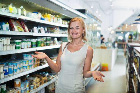 Foto für Smiling young woman standing among shelves in grocery store - Lizenzfreies Bild