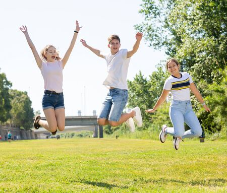 Photo pour Friendly teenagers jumping together in park on spring - image libre de droit