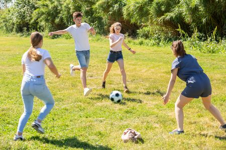 Photo pour Happy teenage girls and guy playing football on green lawn in summer city park - image libre de droit