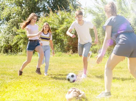 Photo pour Cheerful teenagers are jogning with ball in spring park - image libre de droit