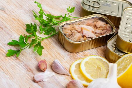 Photo for Tin can of natural chopped tuna belly in oil on wooden background with lemon, garlic and parsley - Royalty Free Image