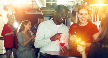 Photo pour Couple of cheerful smiling male and female on party in the club with cocktails - image libre de droit