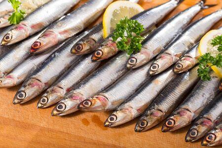 Photo pour Fresh raw anchovies served on wooden surface - image libre de droit