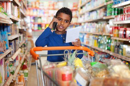 Foto für Focused serious  African tween boy talking on phone and looking at shopping list while visiting supermarket - Lizenzfreies Bild