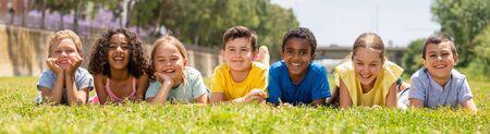 Foto de Portrait of smiling children who are posing lying in the park - Imagen libre de derechos