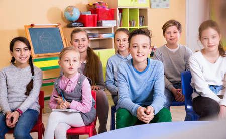 Portrait of pupils listening teacher at lesson in elementary sch