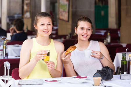 Photo pour female friends traveling and drinking tea with bakery in lunch - image libre de droit