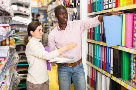 Photo pour Family couple looking document case in stationery shop - image libre de droit