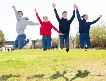 Photo pour Four joyful teens jump on a lawn - image libre de droit