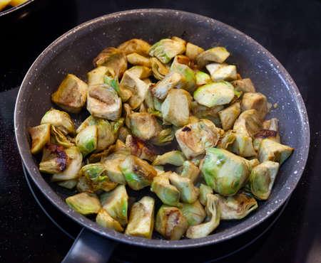 Photo pour Appetizing artichokes fried in a pan - image libre de droit