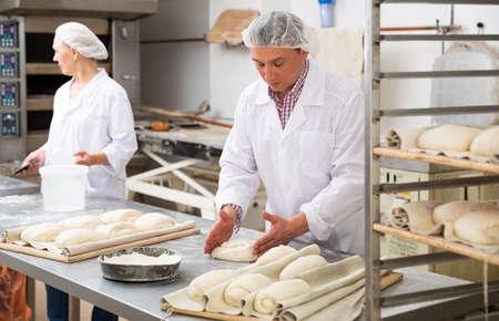 Photo pour Baker forming dough for baking bread - image libre de droit