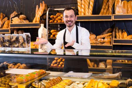 Photo pour Young male seller showing assortment of bakery - image libre de droit