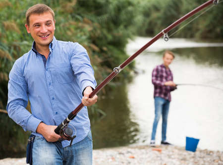 Photo pour man casting line for fishing on river . - image libre de droit