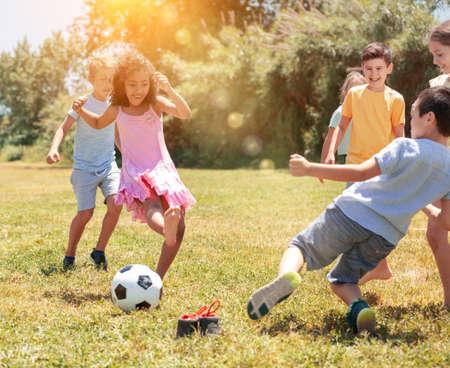 Photo pour Group of happy schoolchildren playing football together - image libre de droit