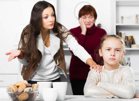 Photo pour Offended little while mom and granny scolding her - image libre de droit