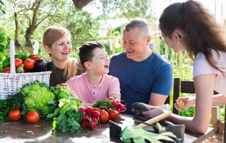Foto für Family talking in garden with gathered vegetables - Lizenzfreies Bild