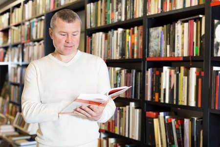 Foto de Man browsing inside of books while visiting library - Imagen libre de derechos