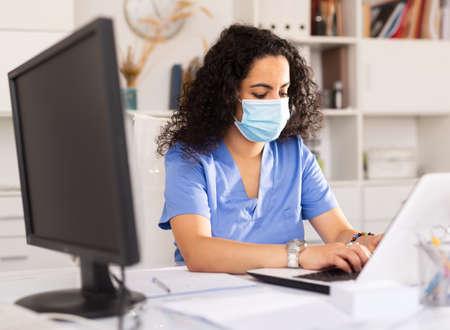 Photo pour Doctor in mask working on laptop - image libre de droit