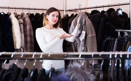 Photo pour Pretty girl customer examining sheepskin coat - image libre de droit