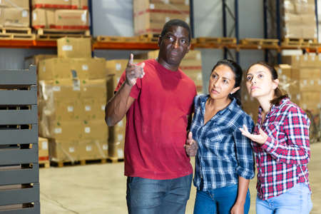 Photo pour Three workers discussing working process at warehouse - image libre de droit