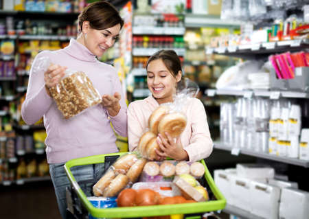 Photo pour Woman with teenage daughter searching for bread - image libre de droit