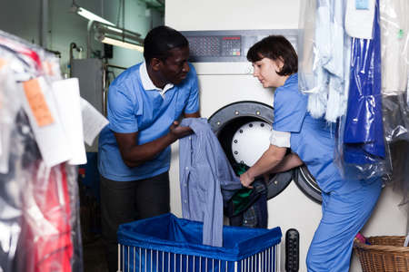 Photo pour Laundry workers loading washing machine - image libre de droit