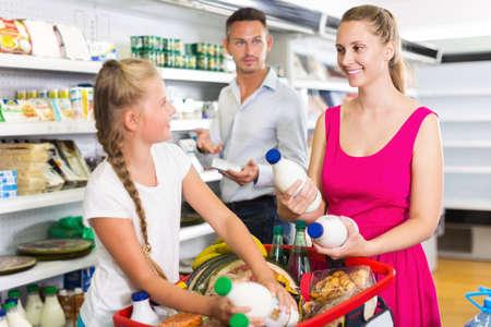 Photo pour Happy young woman with family buying milk - image libre de droit