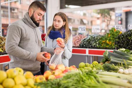 Photo pour Friendly couple examining apples in grocery shop - image libre de droit