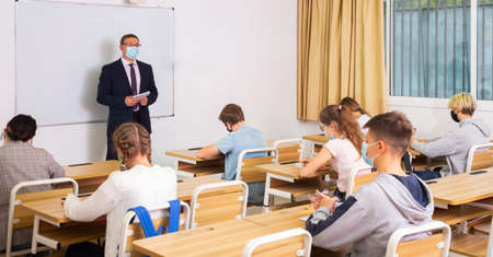 Foto de Male teacher in protective mask giving lesson to teenage students - Imagen libre de derechos