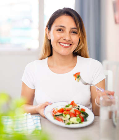 Photo pour Young woman have lunch at home eating freshness salad - image libre de droit
