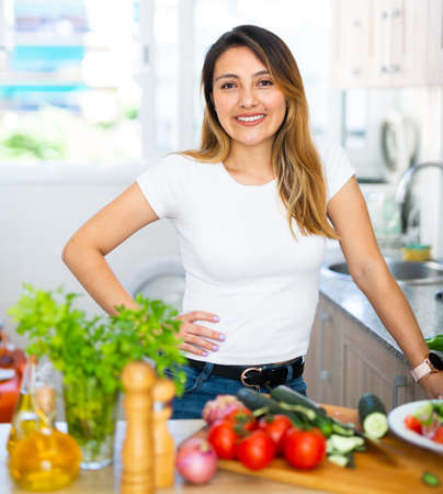 Photo pour Woman is standing near table and cutting vegetables in the kitchen at the home - image libre de droit