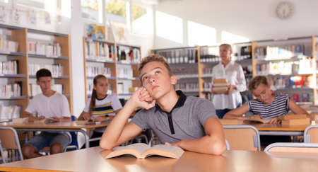 Boy preparing for lesson in school library, reading textbooks