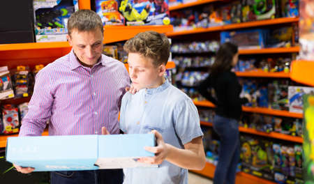 Teenager shopping with father in toy store