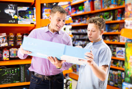 Teenage boy with father buying toys in store
