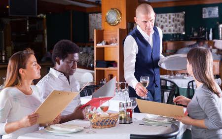 Photo pour male waiter serving order to friends in restaurante - image libre de droit
