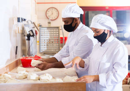 Photo for Male and female baker in protective mask working together in bakery - Royalty Free Image