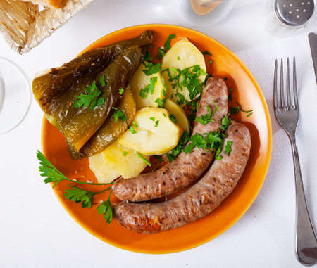 Photo pour Tasty fried pork sausages with baked potatoes and pepper - image libre de droit