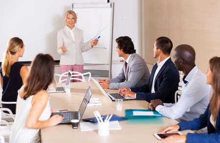 Photo pour Woman making presentation on staff meeting - image libre de droit