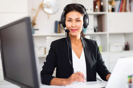 Photo pour Office worker woman is working at a computer and talking by headset with client in office - image libre de droit